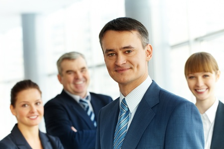 A young businessman smiling against three partners  photo