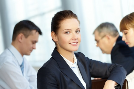 businessteam: A young businesswoman smiling against working colleagues