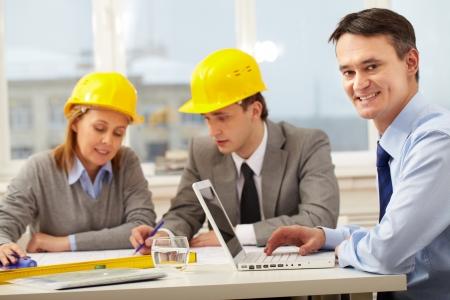 ambiente laboral: Un administrador de trabajar con equipos port�tiles, mirando a la c�mara y sonriente contra sus colegas Foto de archivo