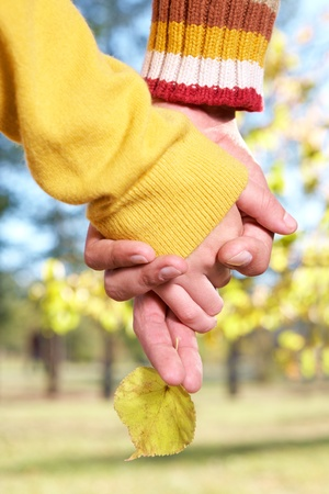 Photo of two human hands holding each other outdoors photo