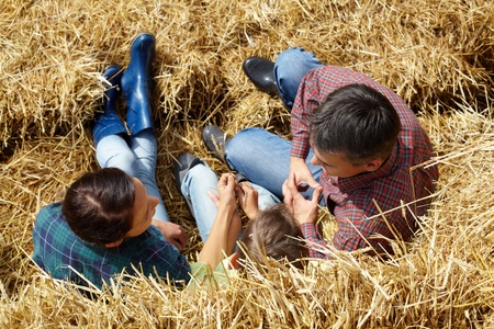 Above angle of family of three having rest in countryside photo