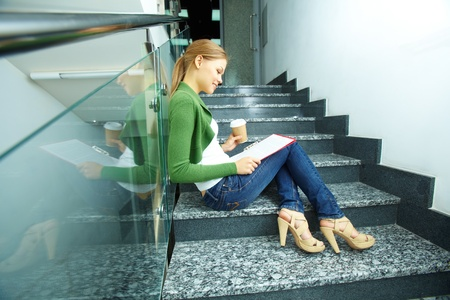 Photo of pretty girl with coffee reading paper on stairs of college photo