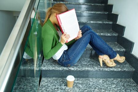 shy woman: Photo of pretty student hiding her face behind paper on stairs of college
