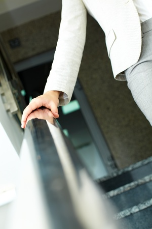 going down: Image of female hand holding by banisters while going down in office building