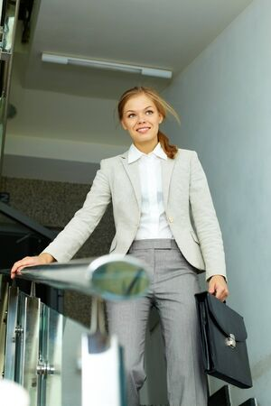 Image of pretty businesswoman with briefcase in the corridor of office building photo