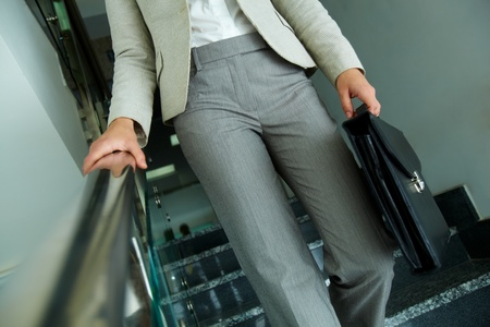 Close-up of businesswoman with briefcase going down the stairway photo