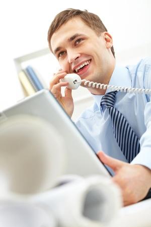 llamando: Hombre de negocios confidente hablando por teléfono en la oficina