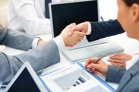 business agreement: Close-up of business partners handshaking in working environment