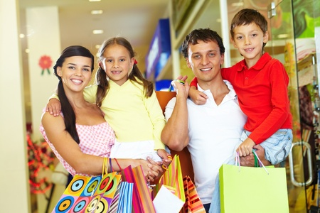 Portrait of happy parents and children with paperbags after shopping photo