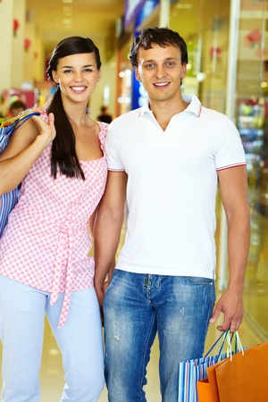 Portrait of happy couple with paperbags during shopping photo