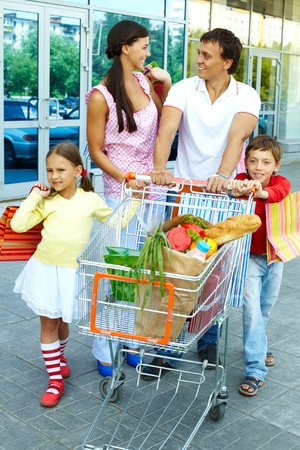 Couple with shopping bags and their two children pushing cart photo