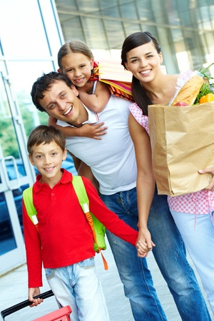 paperbags: Couple with paperbags and their two children after shopping