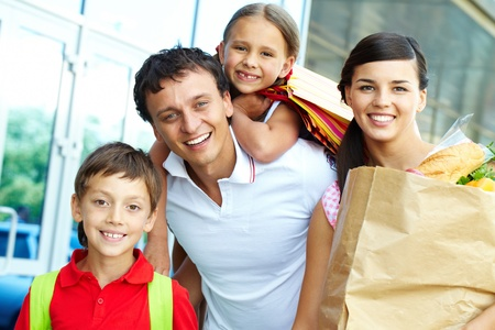 Couple with paperbags and their two children after shopping photo