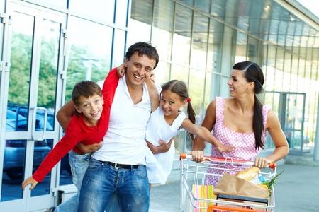 ni�os de compras: Retrato de familia feliz de cuatro personas con carrito de alimentos Foto de archivo