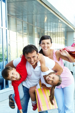 Portrait of happy family of four with shopping bags having fun photo