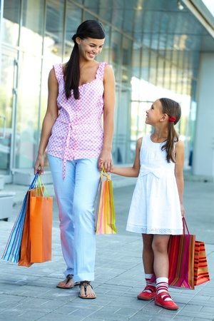 shoppingbag: Portrait of a woman and girl walking with shopping bags Stock Photo