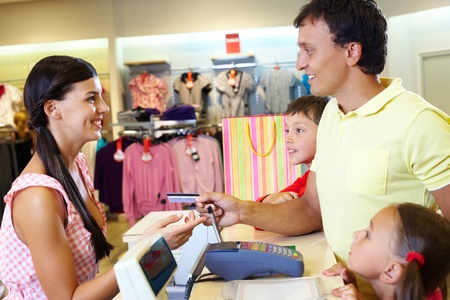 paying with credit card: Man with two children paying for purchases   Stock Photo