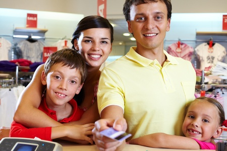 Portrait of family of four giving credit card photo