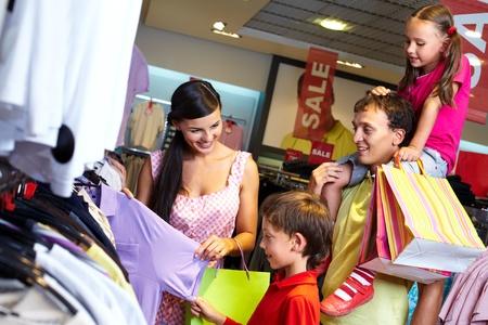 Portret van een familie met boodschappentassen het kiezen van nieuwe kleren in het winkelcentrum Stockfoto