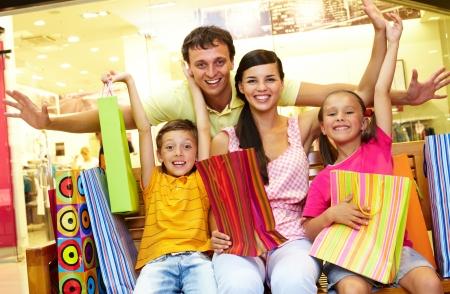 faire les courses: Portrait de famille joyeuse assis dans le magasin avec beaucoup de sacs de magasinage