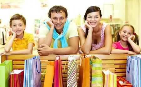 happy rich woman: Ritratto di una famiglia al banco con abbondanza di borse per la spesa guardando la fotocamera e sorridente