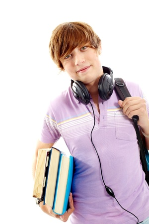 Portrait of teenage boy with books, headphones and backpack looking at camera photo