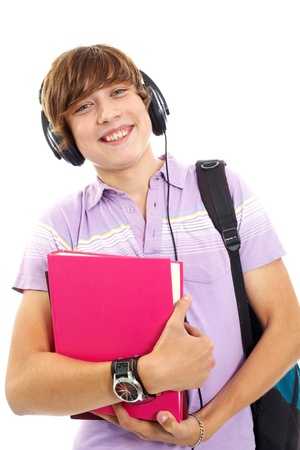 Portrait of happy teenage boy with books, headphones and backpack looking at camera photo