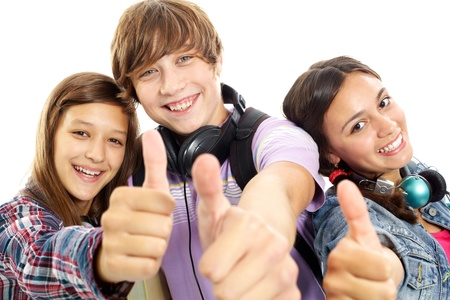 youth group: Cute teens with headphones showing thumbs up and smiling at camera