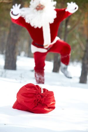 Santa Claus running to his sack lost in winter wood Stock Photo - 10835215