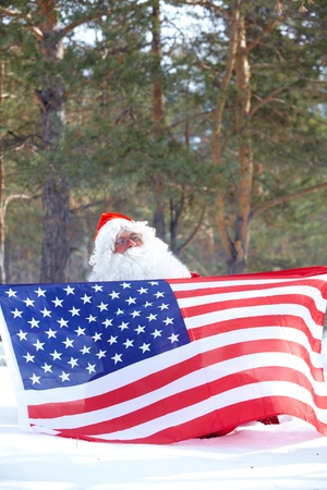 Santa Claus holding American flag in winter forest  photo