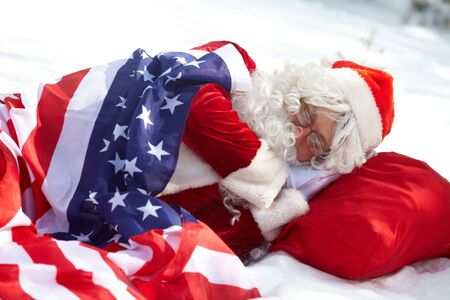 Santa Claus sleeping under American flag in winter forest photo