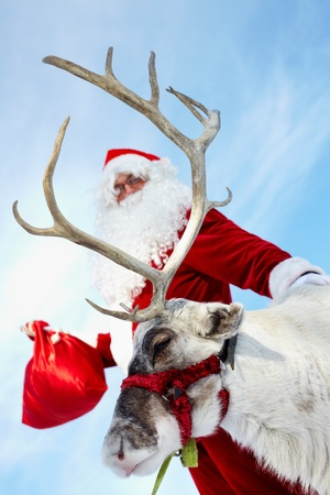 Santa Claus with his reindeer ready for a ride   Stock Photo - 10835253