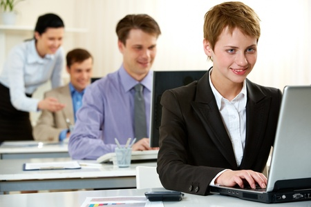 Young woman working on computer in office with other people Stock Photo - 10864337