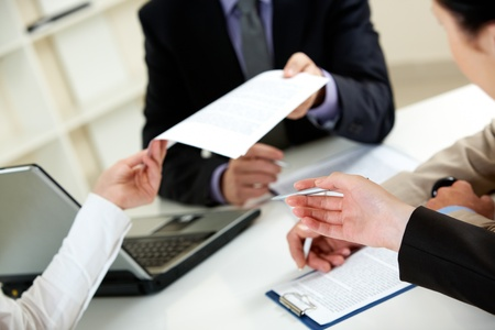 holding close: Businessman giving document to his colleagues