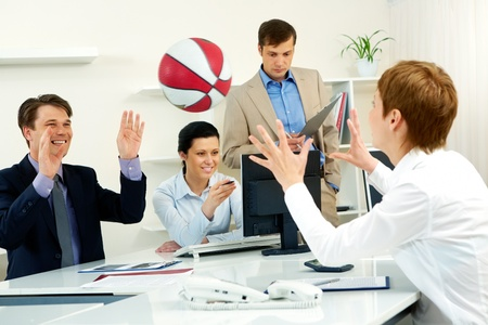 Businesspeople throwing basketball in the office Stock Photo - 10864333