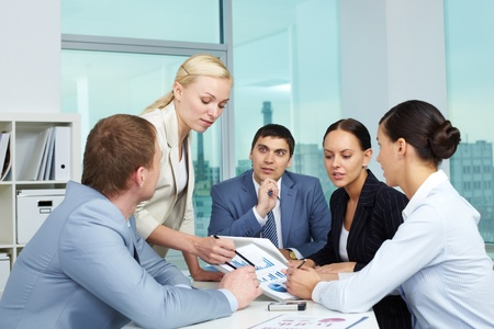 Business people looking at paper with charts Stock Photo - 10864364