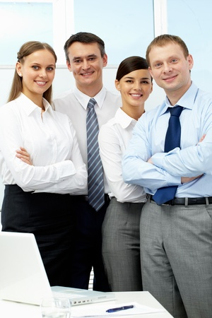 Portrait of four business people looking at camera and smiling photo