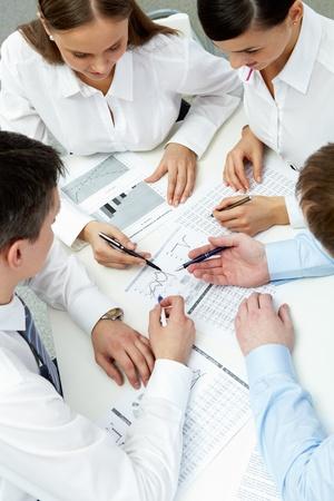 recursos financieros: Gran ángulo visión de cuatro empresarios que trabajan con datos financieros