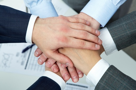 Hands of four businesspeople on top of each other  photo