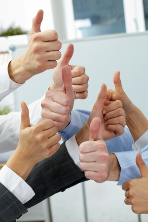 Hands of four businesspeople showing big thumbs Stock Photo - 10864348