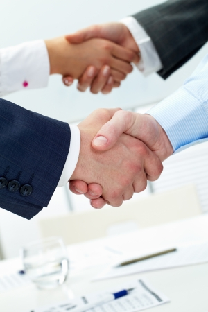 negotiation business: Two pairs of shaking business hands