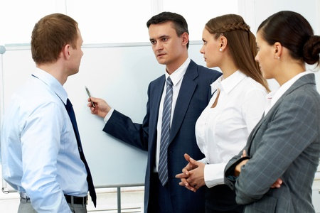 Confident boss explaining something to his colleagues