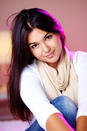 Portrait of pretty brunette girl looking at camera and smiling  photo