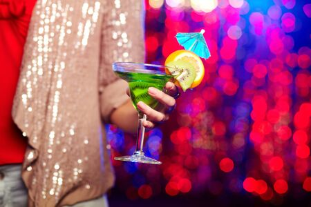 Female hand holding martini glass with cocktail  photo