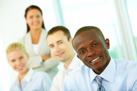Four businesspeople looking at camera and smiling, the focus is on African American Stock Photo - 10882306