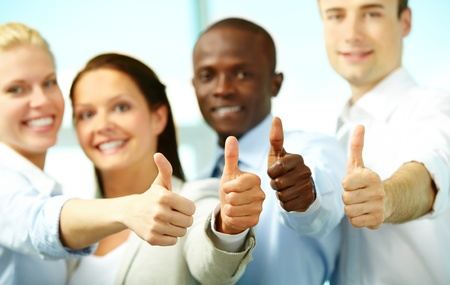 winning woman: Four business people showing big thumbs and smiling at camera Stock Photo