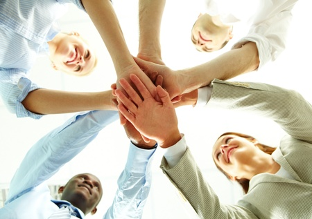 Four business people putting their hands on hands of their colleagues  Stock Photo - 10882301