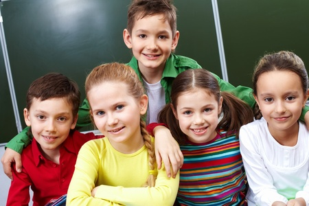 Portrait of happy guys and girls looking at camera in class Stock Photo - 10931288
