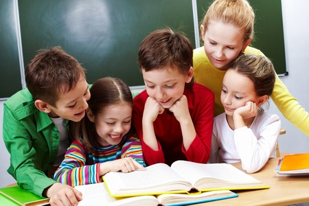 kids reading book: Portrait of friendly group reading book in classroom