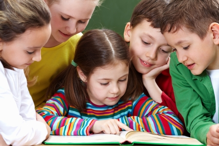 kid pointing: Portrait of friendly group reading book in classroom